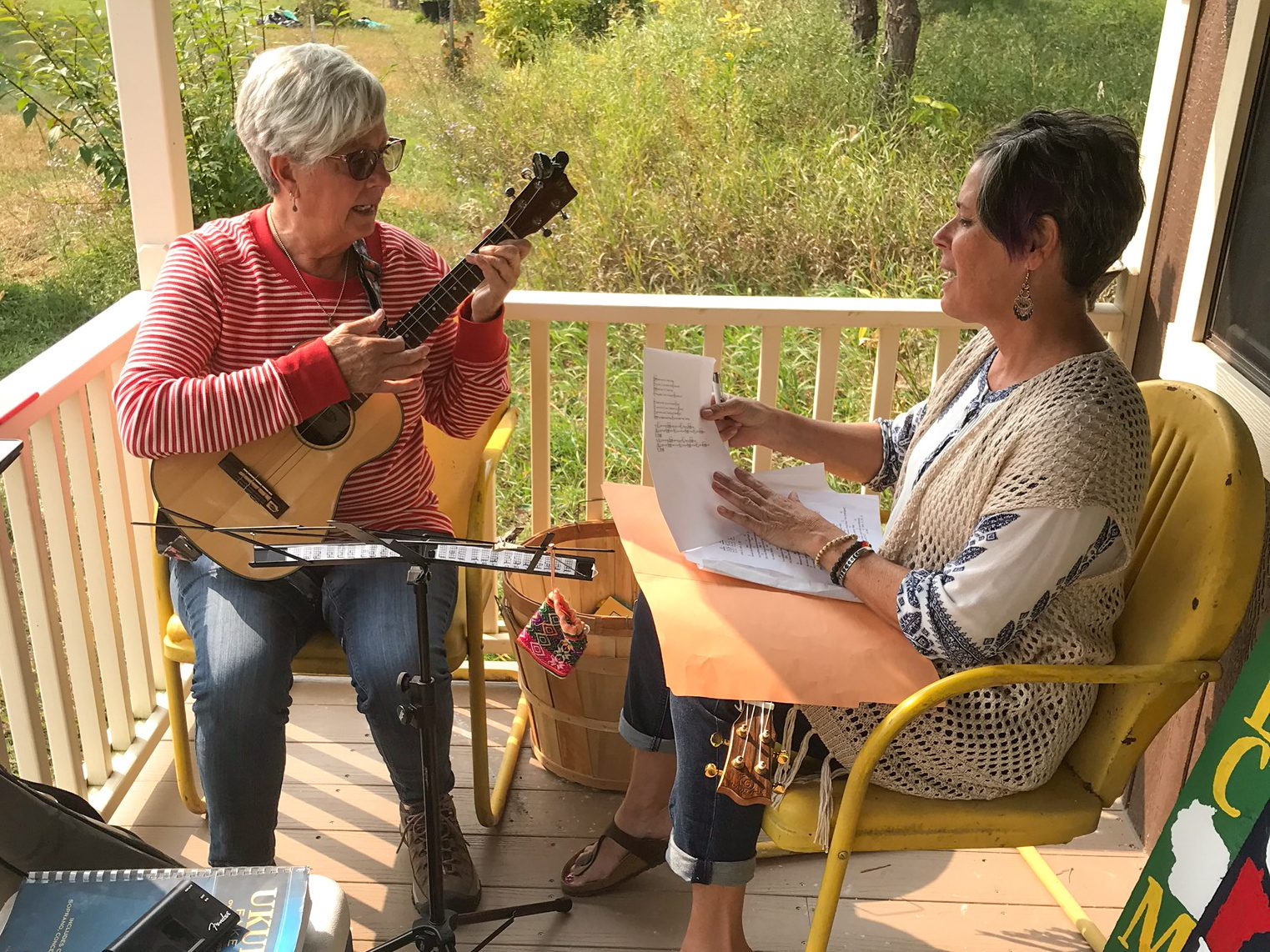Playing the ukulele on the front porch of the cabin shed retail store